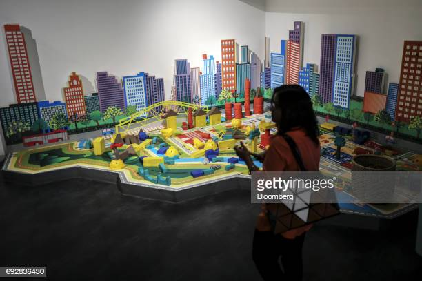 A woman walks near a model in a Lodha Group showroom in Palava City on the outskirts of Mumbai India on Thursday May 25 2017 Lodha best known for its...
