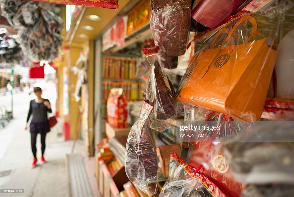 A woman walks near a store selling paper replicas of items used as offerings for deceased relatives and displaying paper luxury bags in Hong Kong on April 29, 2016. Luxury fashion brand Gucci has warned Hong Kong shops selling paper handbags as 'offerings' for the dead not to market items resembling their products. / AFP / AARON TAM