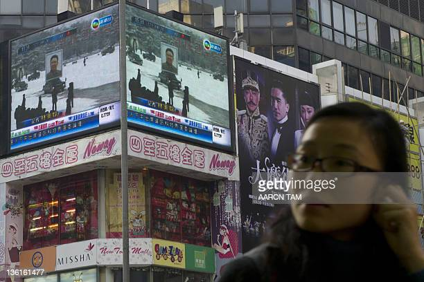 A woman walks near an electronic display in Hong Kong showing a portrait of North Korea's late leader Kim Jongil on top of a car at his funeral in...