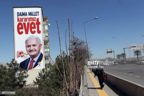 A woman walks near giant poster picturing Turkish Prime Minister Binali Yildirim and reading in Turkish ' 'First our Country of course Yes ' on March...