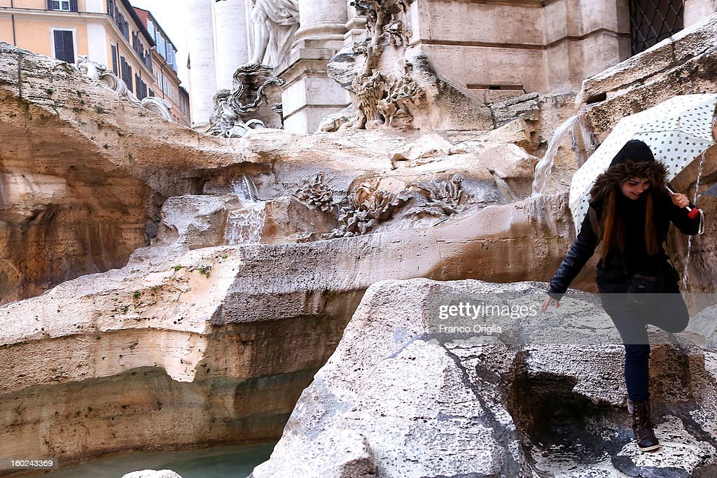 A woman walks near the deteriorated marbles of Trevi Fountain on January 28, 2013 in Rome, Italy. FENDI Chairman and CEO Pietro Beccari together with Karl Lagerfeld and Silvia Venturini Fendi and the representatives of the City of Rome, including the Mayor Gianni Alemanno, today announced the sponsorship of the restoration of Rome's most iconic fountain.