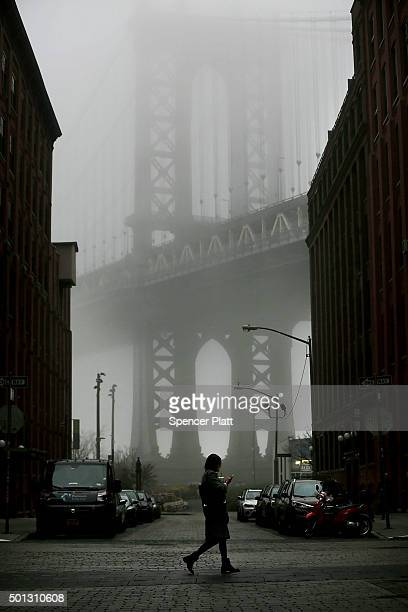 A woman walks near the Manhattan Bridge in morning fog on December 14 2015 in New York City Temperatures across much of the New York metropolitan...