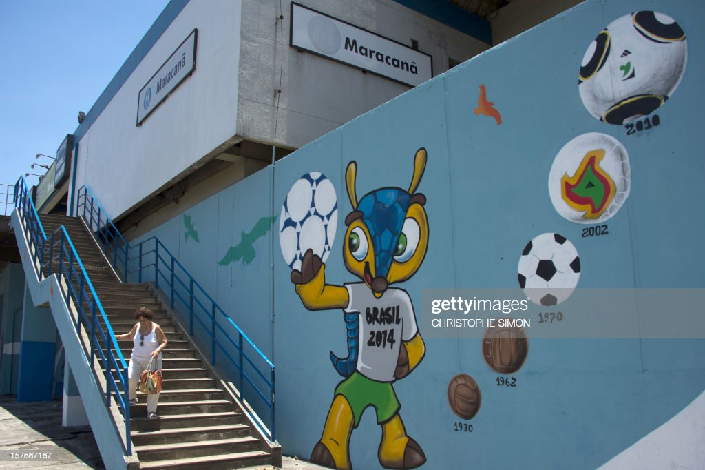 A woman walks next to a graffiti depicting 'Fuleco', the mascot of the Brazil 2014 FIFA World Cup, at the Maracana tube station, next to the Maracana stadium under works, in Rio de Janeiro, Brazil on December 5, 2012.