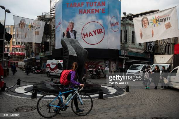 A woman walks next to a 'NO' campain banner on April 6 2017 in Istanbul 10 days ahead of the referendum on whether to change the current...