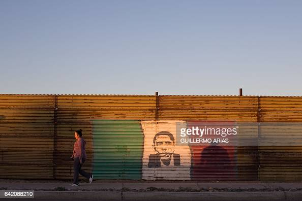 TOPSHOT A woman walks next to a painting of former US President Barack Obama at the US/Mexico border fence in San Luis Rio Colorado Sonora state on...