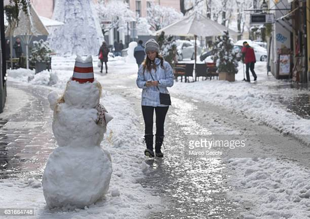 A woman walks next to a snow man along Stari trg on January 14 2017 in Ljubljana Slovenia Most of Slovenia was covered by heavy snowfalls for the...