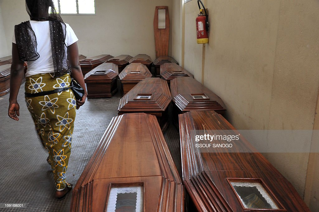 A woman walks next to coffins bearing bodies of people killed in a stampede at the Treichville morgue in Abidjan, on January 9, 2013. The official death toll rose to 63 two days after a New Year stampede, which broke out among crowds returning from a fireworks display in the economic capital Abidjan. AFP PHOTO / ISSOUF SANOGO