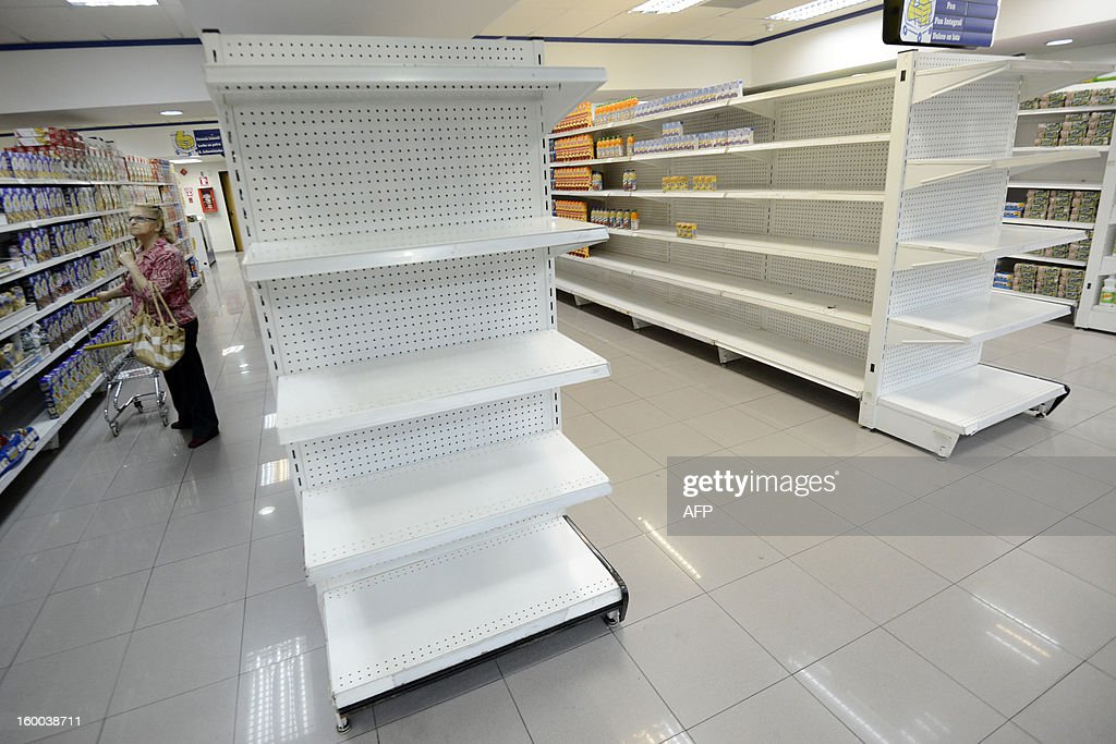 A woman walks next to empty shelves in a supermarket in Caracas on January 22, 2012. According to the Central Bank (BCV) shortage of goods reached 16.3% in December 2012, the highest number in the last four years. AFP PHOTO / Leo RAMIREZ