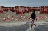 A woman walks next to some 420 panties and portraits of bloodstained womem set up by NGO Rio de Paz to protest against violence against women in...