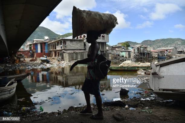 TOPSHOT A woman walks next to the Mapou River in Shadaa neighborhood in CapHaitien in the north of Haiti 240 km from PortauPrince ahead of Hurricane...