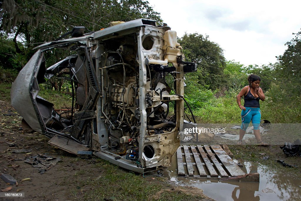A woman walks next to the remains of a car bomb in El Palo, department of Cauca, Colombia, on February 5, 2013. Two car bombs were detonated allegedly by Revolutionary Armed Forces of Colombia (FARC) guerrillas at a military checkpoint in southwestern Colombia Tuesday, killing a civilian and a soldier, and injuring three soldiers. AFP PHOTO/LUIS ROBAYO
