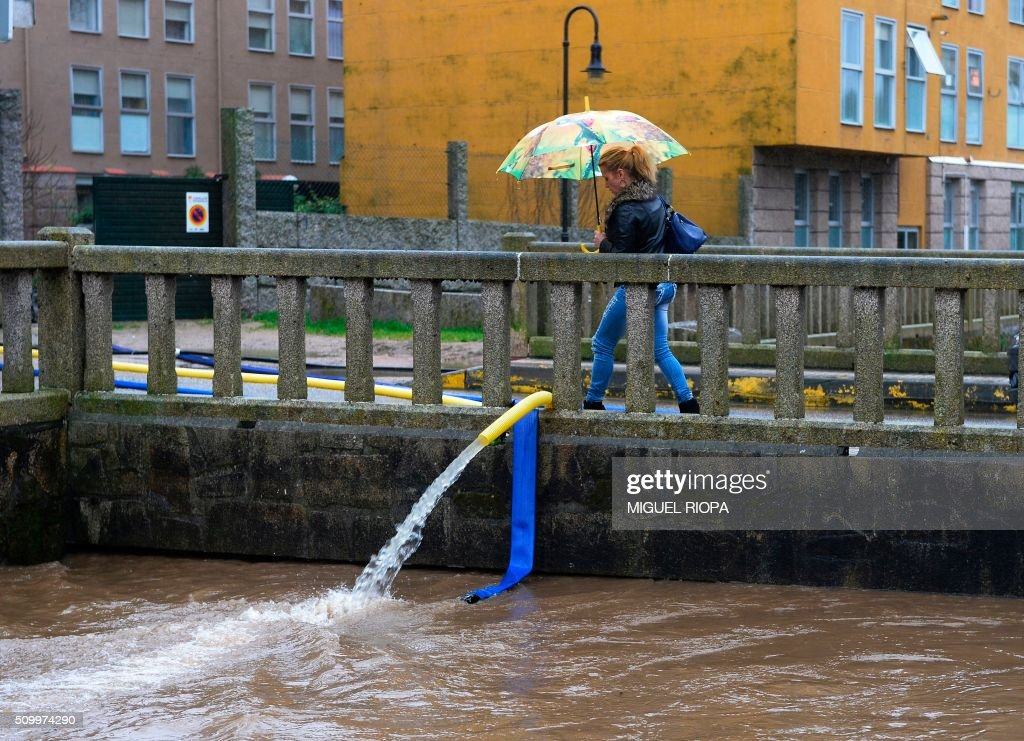 A woman walks on a bridge in a flooded area after heavy rains in the village of Redondela, northwestern Spain, on February 13, 2016. / AFP / AFP or licensors / MIGUEL RIOPA