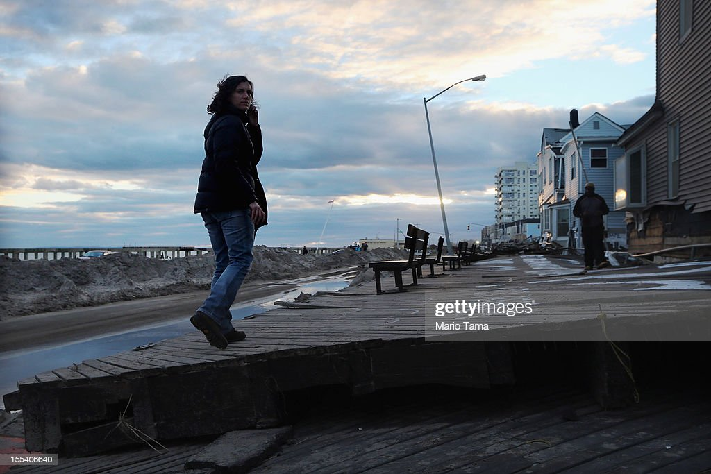 A woman walks on a broken section of boardwalk washed across the street following Superstorm Sandy at Rockaway Beach on November 3, 2012 in the Queens borough of New York City. Most of the Rockaway Peninsula remains without power as colder weather arrives. With the death toll currently over 90 and millions of homes and businesses without power, the US east coast is attempting to recover from the effects of floods, fires and power outages brought on by Superstorm Sandy.