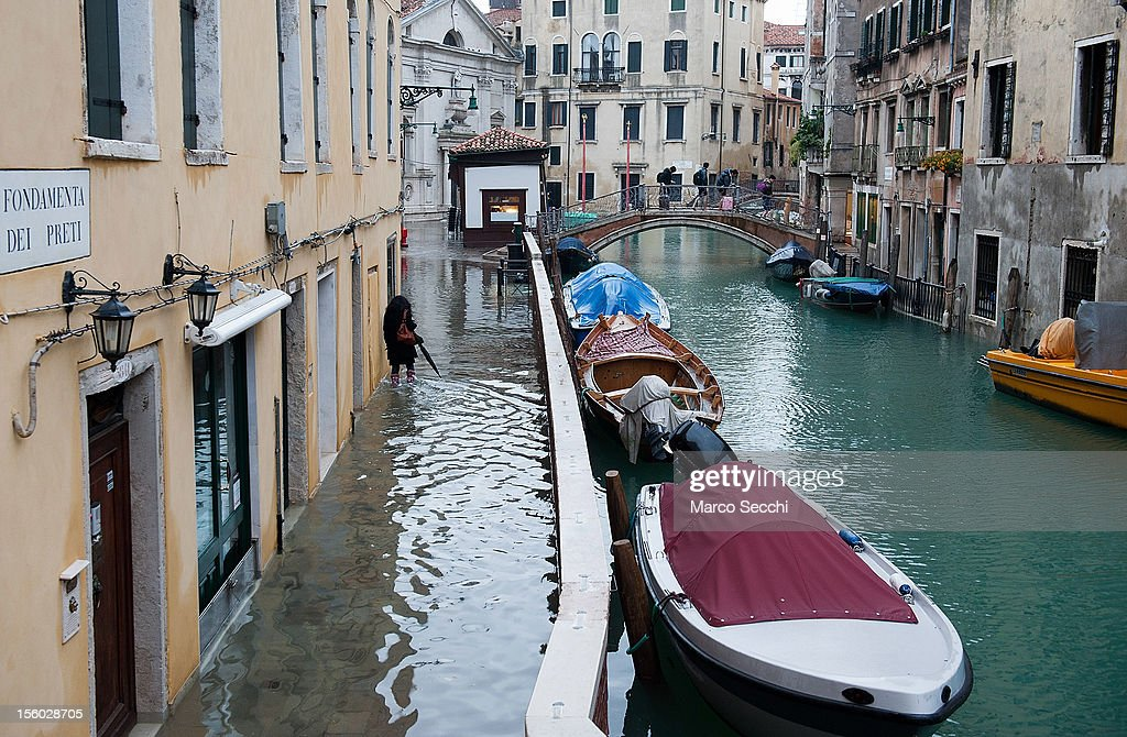A woman walks on a flodded street along a canal during the exceptional High Water on November 11, 2012 in Venice, Italy. More than 70% of Venice has been been left flooded, after the historic town was hit by exceptionally and unexpected high tide. The sea level rose very quickly to 150 due as well to strong southerly wind and heavy rain.