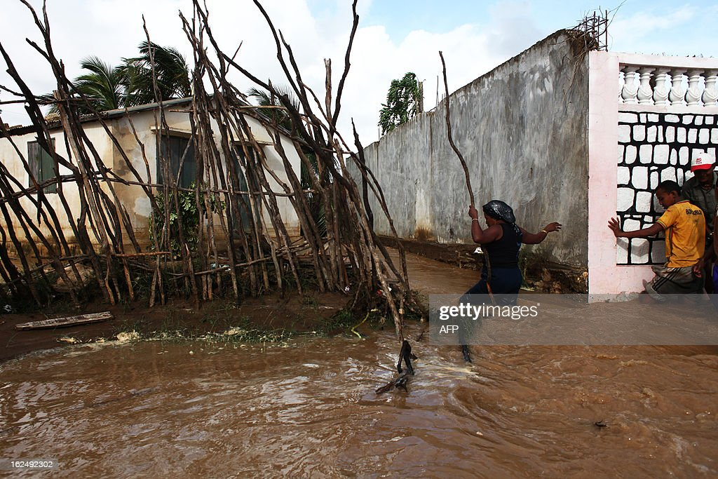 A woman walks on a flooded as she tries to access a destroyed house in Tulear, Madagascar, on February 23, 2013, a day after the cyclone Haruna hit the island.