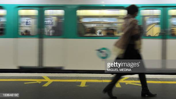 A woman walks on a plateform of Parisian subway as a train arrives on October 28 2010 in Paris Hundreds of thousands of French strikers were due to...