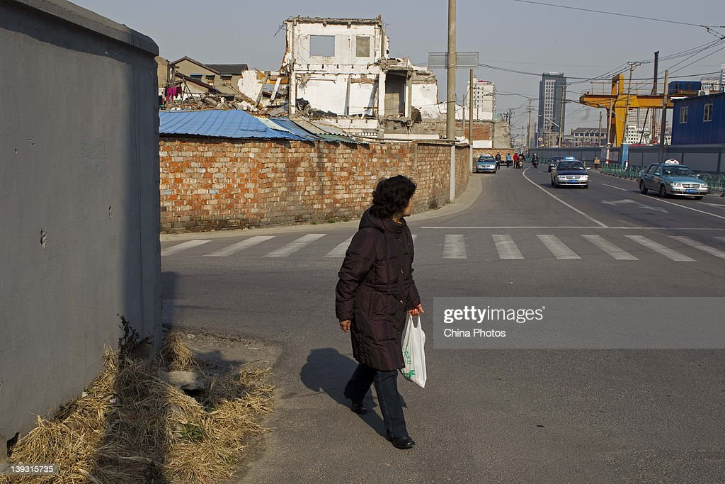 A woman walks on a road at the North Bund on February 19, 2012 in Shanghai, China. According to local media, the North Bund area will be reconstructed as a international shipping and financial zone, a modern commercial and high-end residential area, and recreation center.