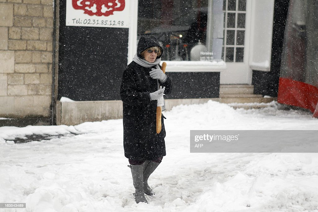 A woman walks on a snowy sidewalk, on March 12, 2013 in Caen, northwestern France, during a heavy snow storm on France. Overnight Monday nearly 500 cars were blocked near Cherbourg where snowdrifts piled up 60 centimetres (almost two feet) as winds reached 100 kilometres (more than 60 miles) an hour. Twenty-six regions in northwest and northern France were put on orange alert because of heavy snowfalls, which Meteo France said were 'remarkable for the season because of the expected quantity and length of time'. AFP PHOTO / CHARLY TRIBALLEAU