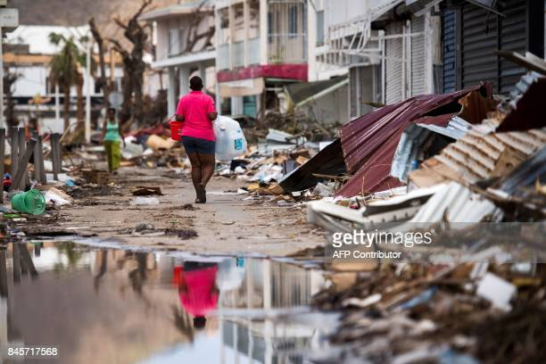 TOPSHOT A woman walks on a street in Marigot on September 11 2017 on the French Caribbean island of SaintMartin after it was hit by Hurricane Irma /...