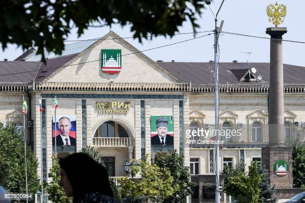 A woman walks on an avenue named after Russian President Vladimir Putin in front of the Grozny city administration's building displaying portraits of...