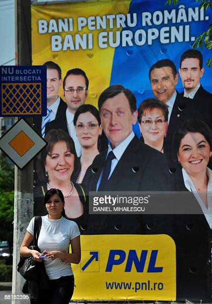 A woman walks on June 2 2009 on a street in Bucharest in front of a billboard of National Liberal Party candidates for the June 7 EU parliamentary...