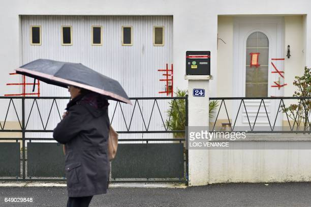 A woman walks on March 7 2017 in Orvault western France in front of the police sealed entrance of the house of the Troadec family the day after the...