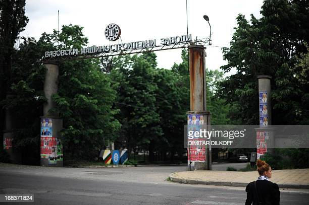 A woman walks on May 8 in the town of Sopot in front of the gate of the country's largest military contractor VMZSopot which provided employment to...