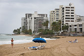 A woman walks on the beach on July 1 2015 in San Juan Puerto Rico The island's residents are dealing with increasing economic hardships and a...