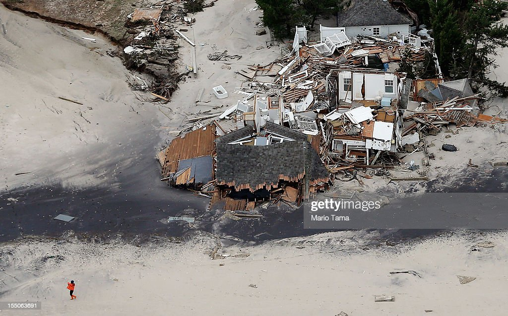 A woman walks on the beach past homes destroyed by Hurricane Sandy on October 31, 2012 in Mantoloking, New Jersey. At least 50 people were reportedly killed in the U.S. by Sandy with New Jersey suffering massive damage and power outages.