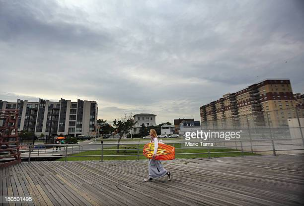 A woman walks on the boardwalk at Rockaway Beach on August 19 2012 in the Queens borough of New York City Over the last few years the Rockaways...