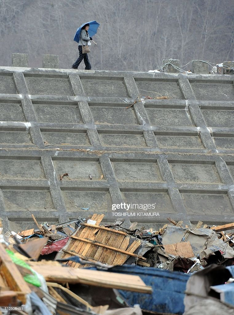 A woman walks on the breakwater wall at the Taro area in Miyako city, Iwate prefecture on April 19, 2011. The Japanese government urged local authorities, businesses and citizens not to discriminate against evacuees from the area around the crippled Fukushima nuclear plant.