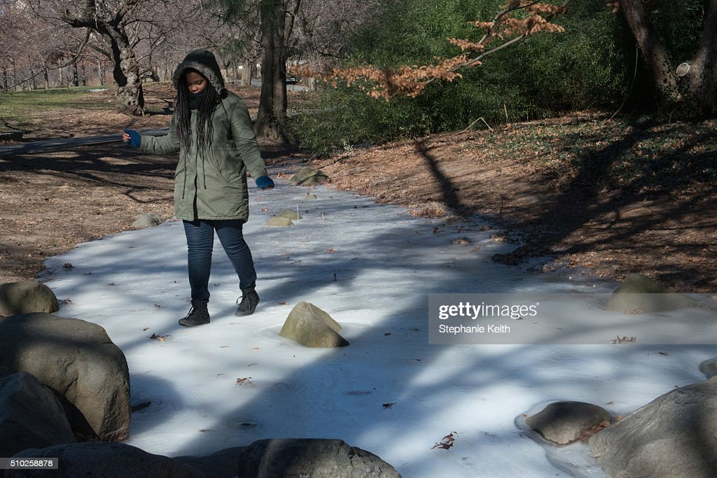 A woman walks on the ice of a frozen stream at the Brooklyn Botanic Garden during an arctic chill that brought frigid temperatures on February 14, 2016 in the Brooklyn borough of New York City. The city broke a 100-year record February 14, as emputures dropped minus 1 degree Fahrenheit.