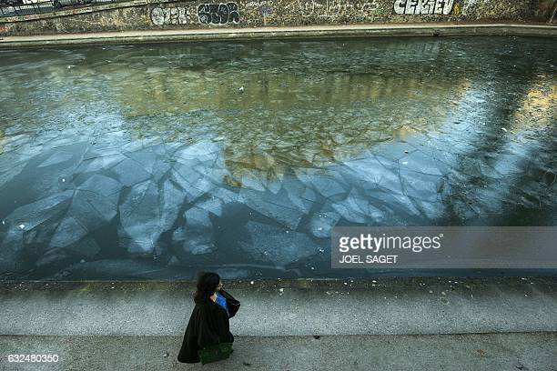 A woman walks on the quay along the frozen Ourcq canal in Paris on January 23 2017 / AFP / JOEL SAGET