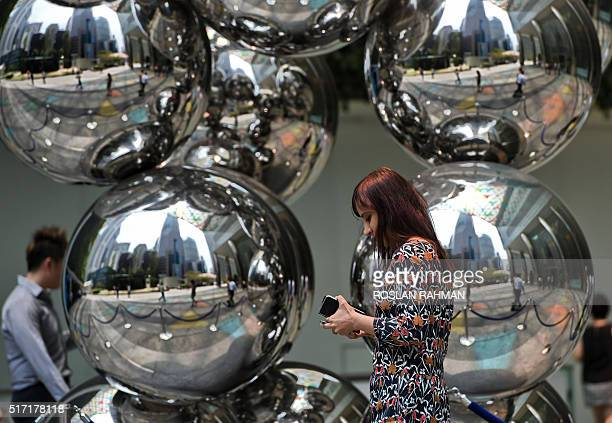 A woman walks out for lunch past a sculpture at the Raffles Place financial district in Singapore on March 24 2016 Singapore's finance minister Heng...