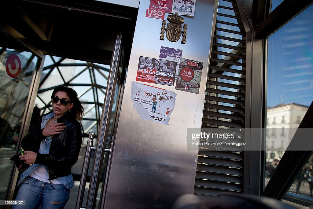 A woman walks out from Sol Station next to a Spanish shield and stickers that read 'N14 General Strike' on November 13, 2012 in Madrid, Spain. Spain's trade unions have called a general strike for November 14, the second general strike during Mariano Rajoy's presidency. Protestors from social movements are expected to join striking public sector workers to protest against austerity cuts and labour reforms. Spain's unemployment rate has now reached 25 per cent.