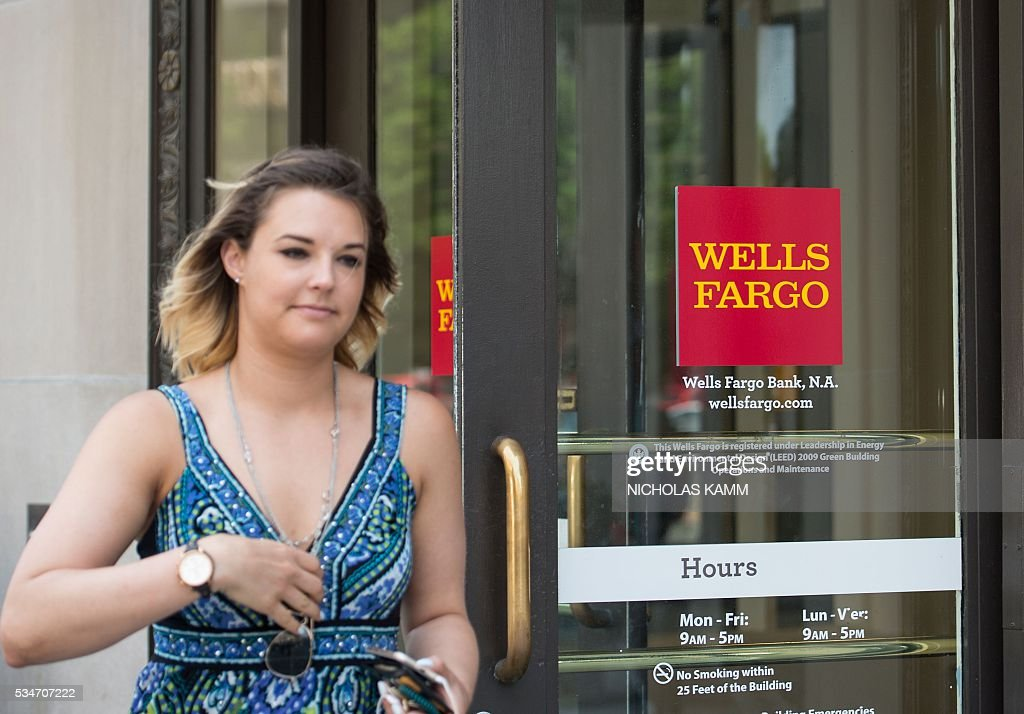 A woman walks out of a Wells Fargo bank in Washington, DC, on May 27, 2016. Wells Fargo is heavily leveraged to the American economy, which banks have said continues to show solid, if slow, improvement. / AFP / Nicholas Kamm