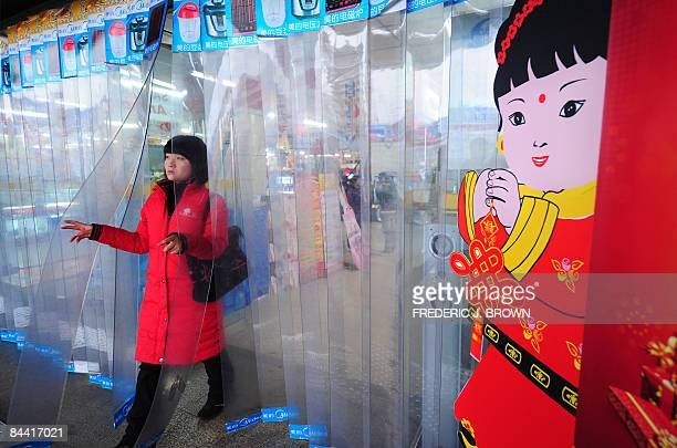 A woman walks out of an electronics and home appliance department store in Zhengzhou on January 19 2009 in central China's Henan province past a...