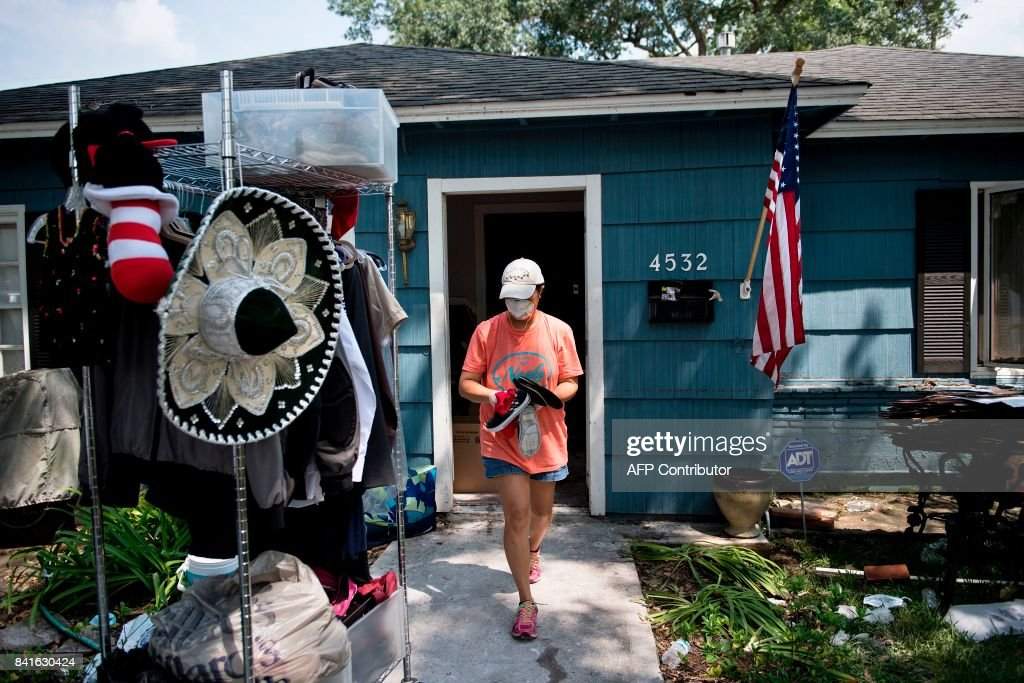 A woman walks out of her home with personal items salvaged from a once flooded house as residents begin the recovery process from Hurricane Harvey on September 1, 2017 in Houston, Texas. / AFP PHOTO / Brendan Smialowski