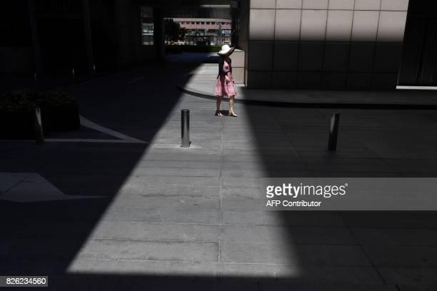 A woman walks outside a shopping mall in Beijing on August 4 2017 / AFP PHOTO / Greg Baker