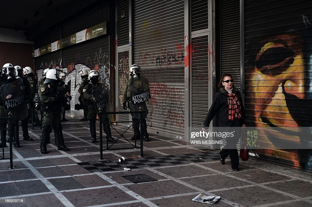 A woman walks outside the Labour Ministry guarded by riot police in Athens on January 30, 2013. Police were called in on Wednesday to dislodge around 30 Communist unionists from the labour ministry in a protest against new pension cut plans. The unionists were arrested and police used tear gas outside the building to disperse a larger group of protesters demanding their release.