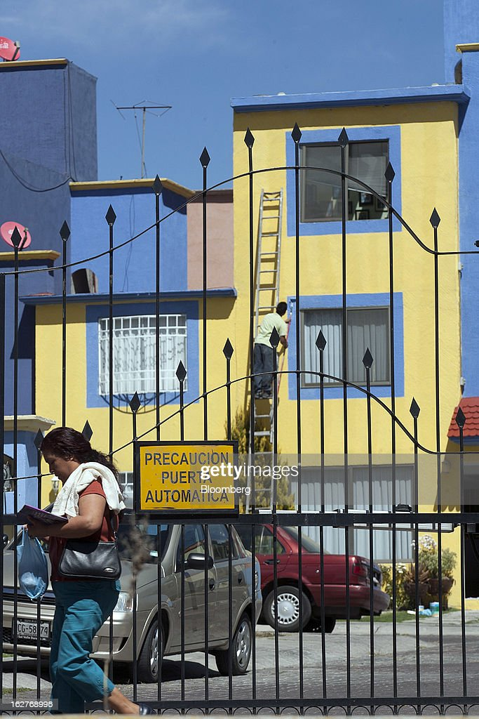 A woman walks outside the Urbi Desarrollos Urbanos SAB's Urbi Quinta Montecarlo housing development in Cuautitlan Izcalli, Mexico, on Monday, Feb. 25, 2013. Urbi Desarrollos Urbanos SAB, the Mexican homebuilder that lost three-fourths of its market value in the past year, will report negative free cash flow to equity for the fourth quarter of 2012, according to a company official with direct knowledge of the matter. Photographer: Susana Gonzalez/Bloomberg via Getty Images