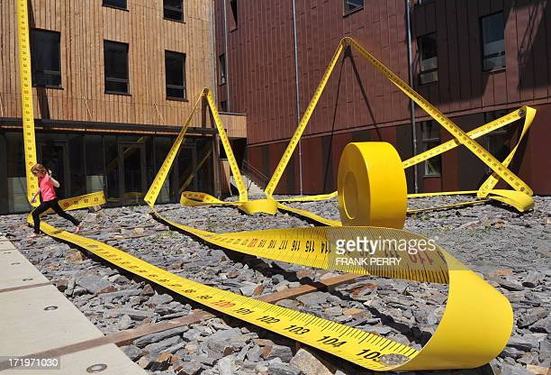 A woman walks over Lilian Bourgeat's 'Tape Measure' a 136 metre oversized object one of the creations displayed in the centre of Nantes western...