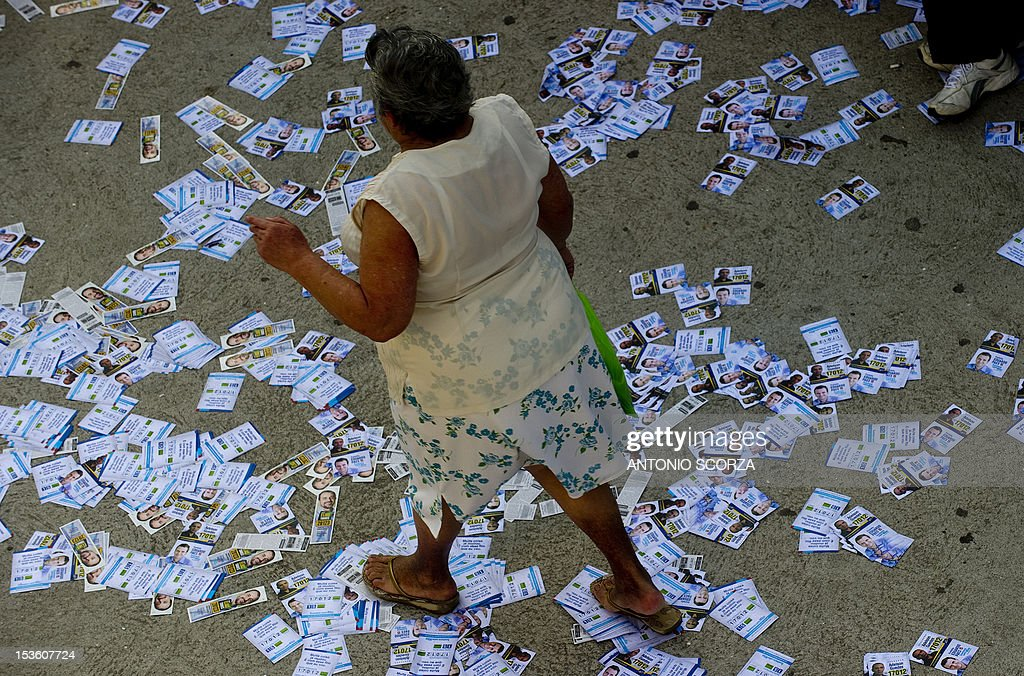 A woman walks over pamphlets as she heads to a polling station in Rio de Janeiro's Rocinha shantytown, Brazil, on October 7, 2012 during the nationwide municipal elections. Nearly 139 million Brazilians are registered to elect 5,561 mayors and 48,000 municipal councilors among 450,000 candidates representing more than 20 political parties.