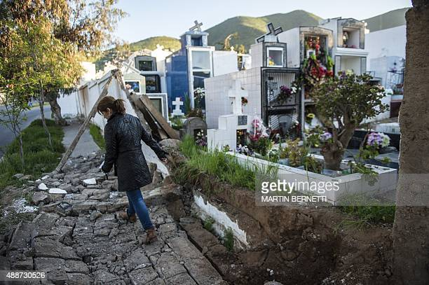 A woman walks over rubble next to a cemetery after an earthquake in Illapel some 200 km north of Santiago on September 17 2015 A powerful 83magnitude...