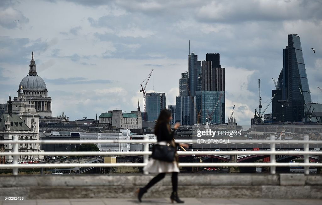A woman walks over Waterloo bridge with a backdrop of St Paul's Cathedral and buildings in City of London in central London on June 27, 2016. Britain began preparations to leave the European Union on Monday but said it would not be rushed into a quick exit, as markets plunged in the wake of a seismic referendum despite attempts to calm jitters. / AFP / BEN