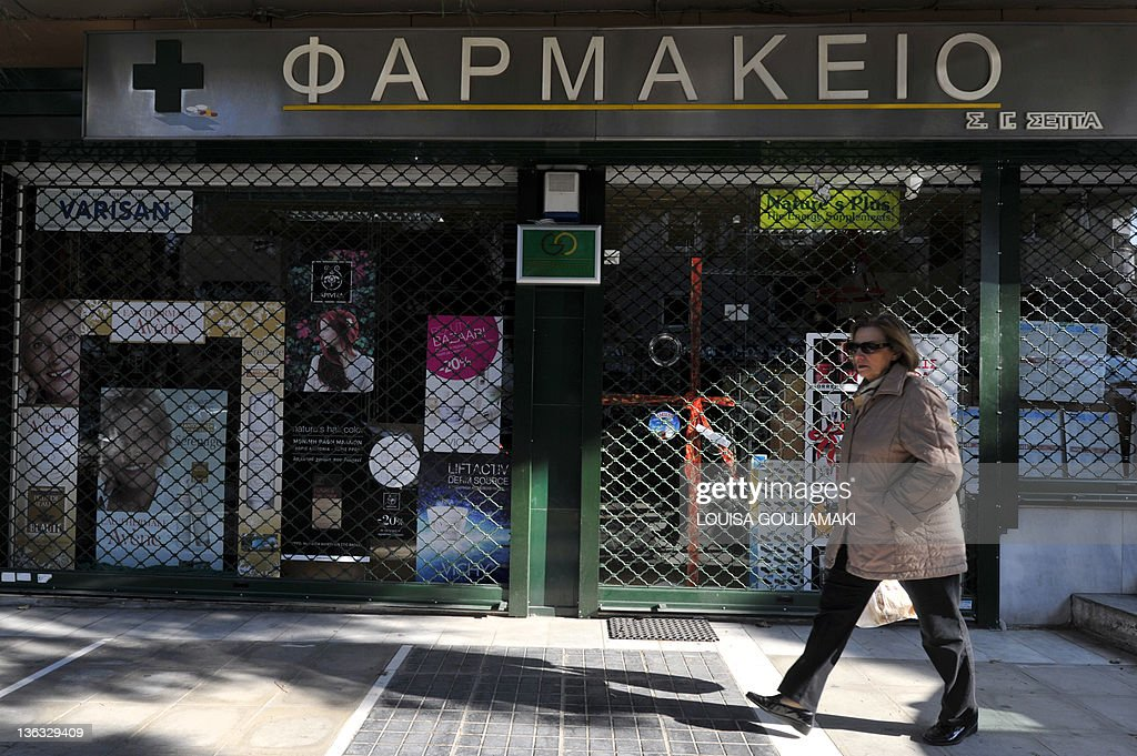 A woman walks pass a shut pharmacy in central Athens at the start of a rolling 48hour strike on January 2 2012 Greek pharmacists and doctors today...