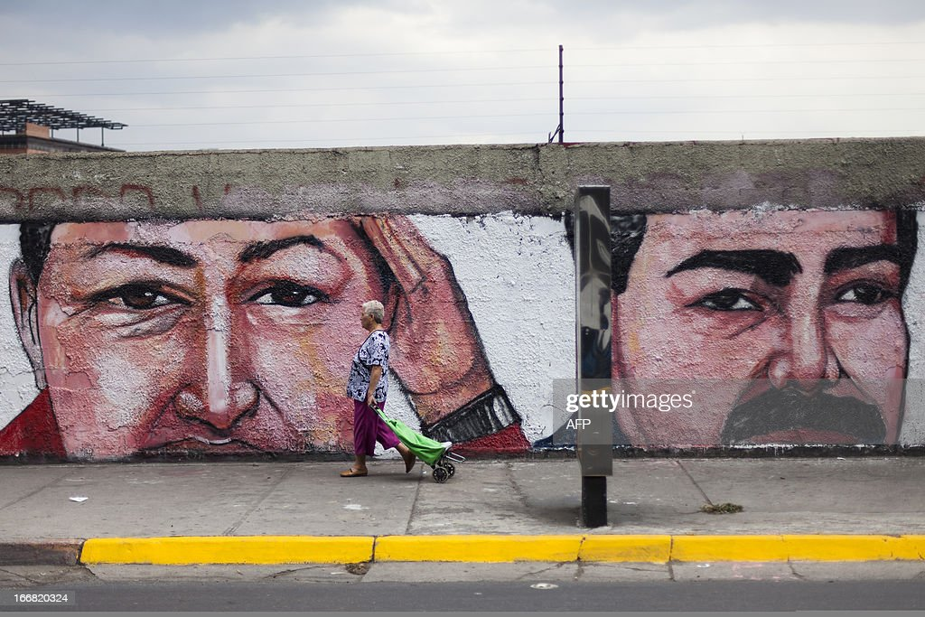 A woman walks pass in front of a graffiti depicting Venezuelan late President Hugo Chavez (L) and Venezuelan President Nicolas Maduro (R) in Caracas on April 17, 2013. Tensions ran high in Venezuela Wednesday in the wake of deadly demonstrations sparked by a disputed weekend election in which Hugo Chavez's hand-picked leftist heir won by a razor-thin margin. The Supreme Court said a manual recount of ballots demanded by the defeated candidate would be impossible because voting has been computerized since 1999, as the United States sided with the opposition in calling for a new tally. AFP PHOTO / Leo RAMIREZ