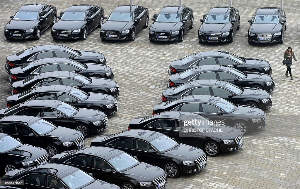 A woman walks passes several black Audi limousines arriving on the premisses of the German carmaker's headquarter in Ingolstadt, southern Germany, on March 12 , 2013 prior to the company's annual press conference. German carmaker Audi, the top-of-the-range subsidiary of European auto giant Volkswagen, said Tuesday, March 12, 2013 it booked record sales in 2012 and hopes to achieve further growth this year. AFP PHOTO/CHRISTOF STACHE