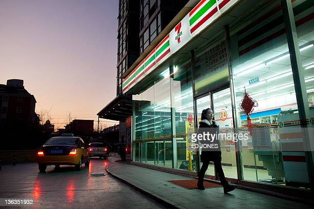 A woman walks past a 7Eleven convenience store in Beijing on January 3 2012 There are some 600 7Eleven stores in the Chinese capital though plans to...