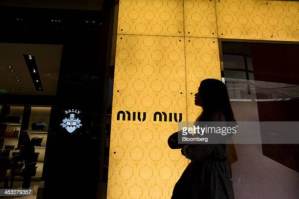 A woman walks past a Bally International AG store left and a Prada SpA Miu Miu store inside the TaiKoo Hui shopping mall operated by Swire Properties...